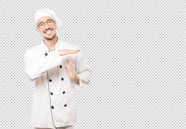 그의 손으로 시간 초과 제스처를 만드는 친절한 젊은 요리사