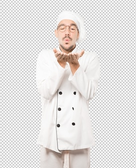 Friendly young chef making a gesture of sending a kiss with his hand