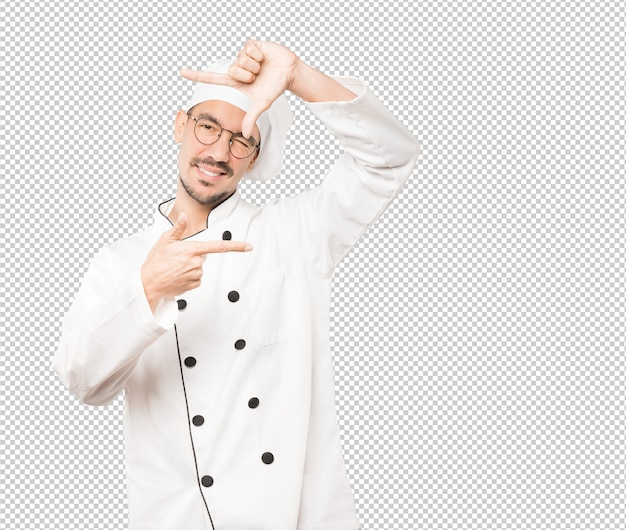 Friendly young chef making a gesture of taking a photo with the hands