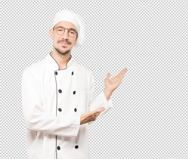 Friendly young chef making a gesture of welcome