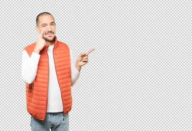Дружелюбный молодой человек делает жест осторожности с его рукой, указывающей на его глаз