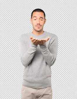 Дружелюбный молодой человек делает жест, отправляя поцелуй рукой