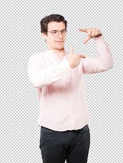 손으로 사진을 찍는 제스처를 만드는 친절한 젊은이