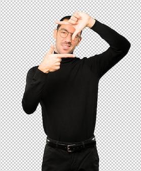 手で写真を撮るジェスチャーをするフレンドリーな若い男