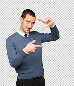 Дружелюбный молодой человек делает жест фотографирования руками