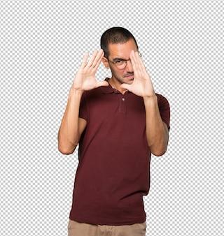 손으로 사진을 찍는 제스처를 취하는 친절한 청년