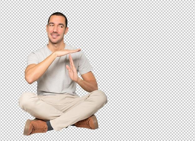 Дружелюбный молодой человек, делая жест тайм-аут руками Premium Psd