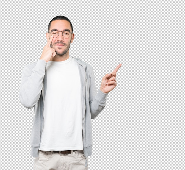Friendly young man making a gesture of being careful with his hand pointing at his eye