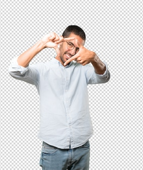Friendly young man making a gesture of taking a photo with the hands