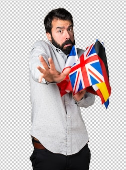 Frightened handsome man with beard holding many flags