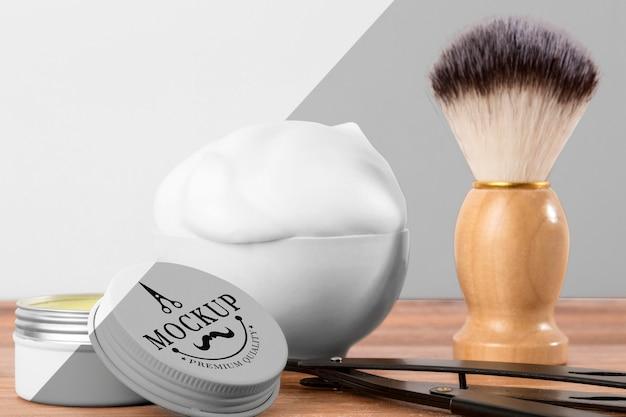Vista frontale dei prodotti da barbiere con pennello e schiuma