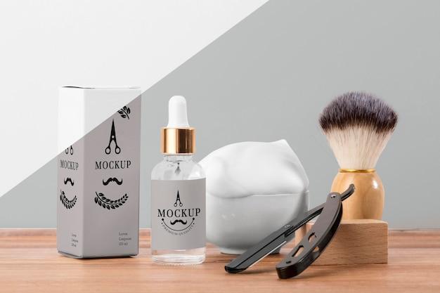 Vista frontale dei prodotti da barbiere con pennello e siero