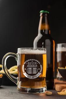 Vista frontale della bottiglia di birra e pinta con assortimento di snack
