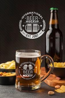 Vista frontale della pinta di birra e bottiglia con assortimento di snack