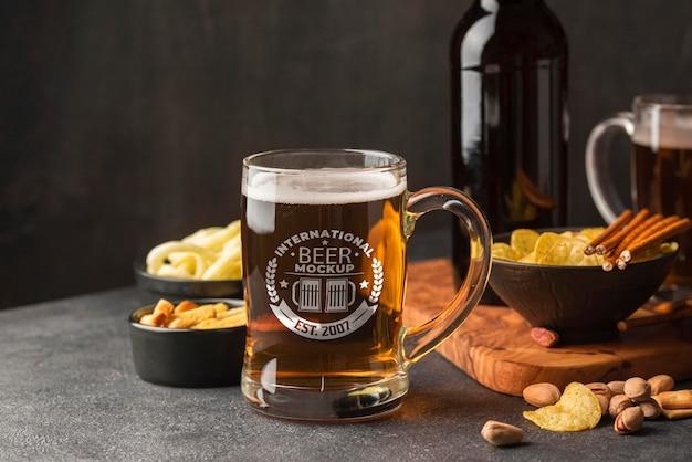 Vista frontale della pinta di birra con assortimento di snack
