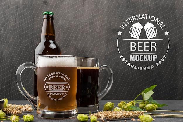 Vista frontale di pinte di birra e bottiglia con orzo