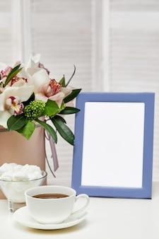 ピンクのテーブルの上のフォトフレームの正面空モックアップ。蘭の花、お茶やお菓子。