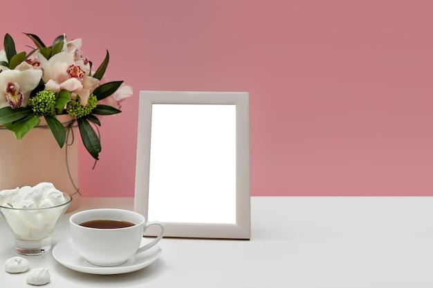 Вид спереди пустой макет фоторамки на розовом столе. цветы орхидеи, чашка чая и сладости.