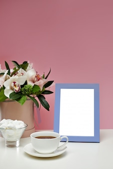 Front view blank mockup of photo frame on the pink table. orchid flowers, cup of tea and sweets.