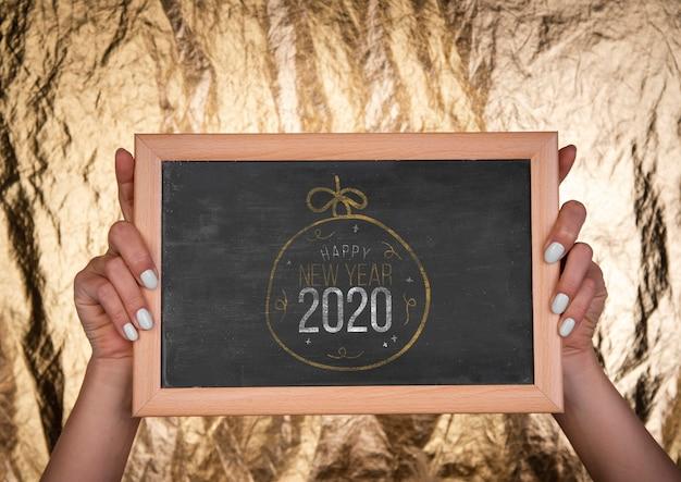 新年のモックアップテキストと手で正面図黒板