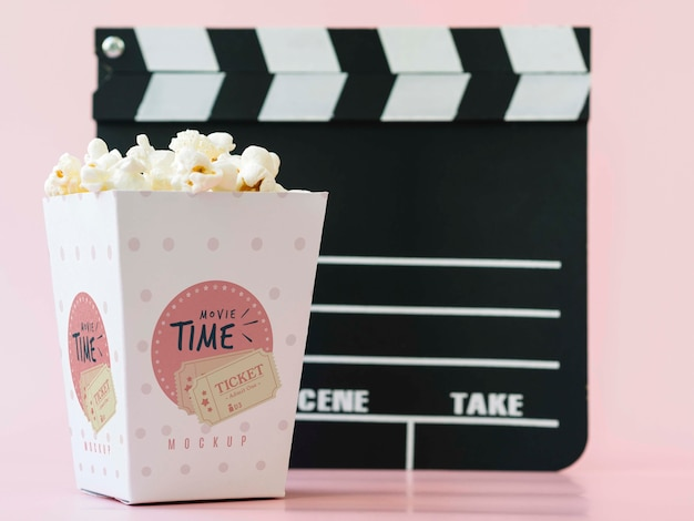 Front view of cinema clapperboard and popcorn