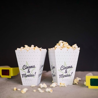 Front view of cinema glasses and cups of popcorn