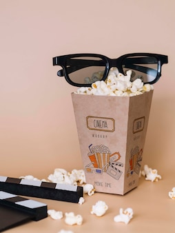 Front view of cinema popcorn in cup with glasses