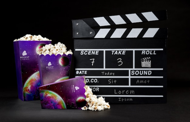 Front view of cinema popcorn cups with clapperboard