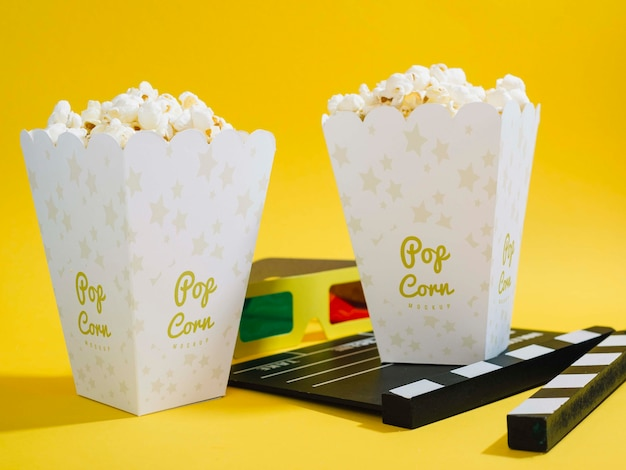 Front view of cinema popcorn in cups with glasses and clapperboard