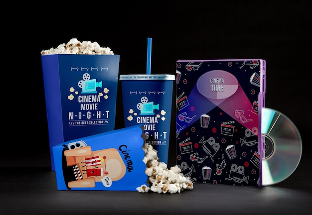Front view of cinema popcorn cups with straw and dvd