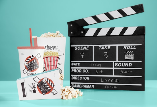 Front view of cinema popcorn with cup and clapperboard