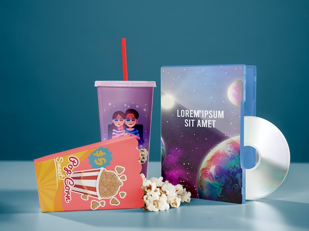 Front view of cinema popcorn with cup and dvd