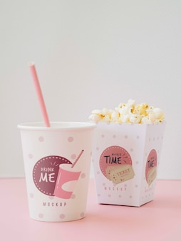 Front view of cups with popcorn and soda for cinema