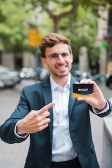 Front view of defocused businessman holding and pointing at business card