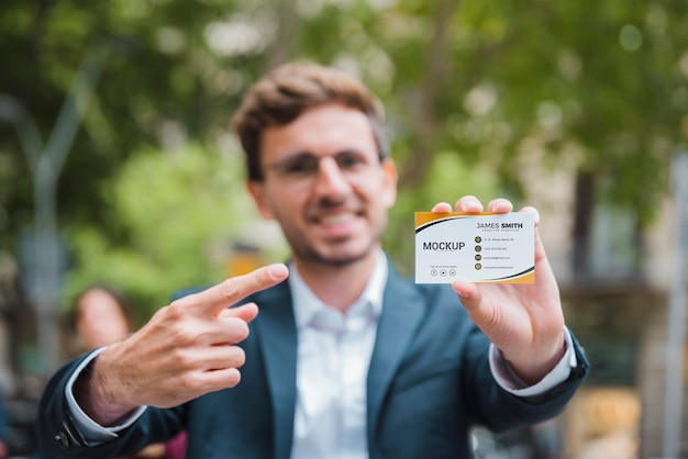 Front view of defocused businessman pointing at and holding a business card