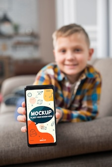 Front view of defocused kid on couch holding smartphone
