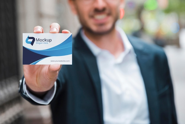 Front view of defocused smiley businessman holding business card
