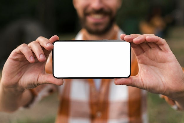 Front view of defocused smiley man holding smartphone while camping