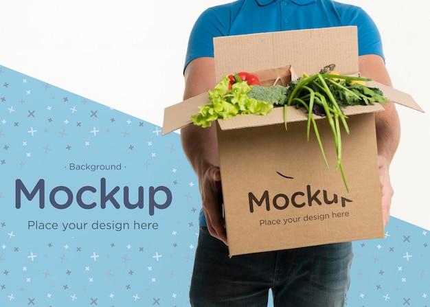Доставка человек вид спереди держит коробку с разными овощами