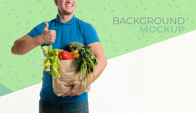 Front view delivery man holding a box with different vegetables mock-up