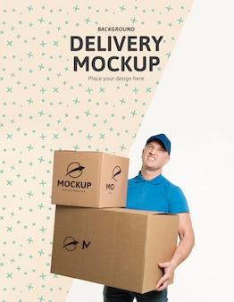 Uomo di consegna di vista frontale che tiene un mazzo di scatole con mock-up di sfondo
