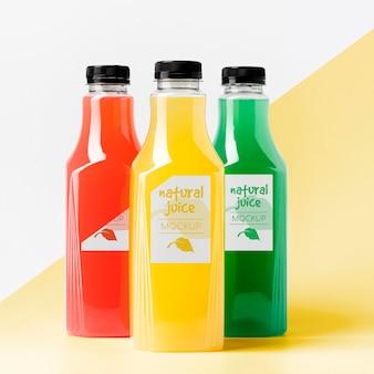 Vista frontale di diverse bottiglie di succo trasparente con tappi