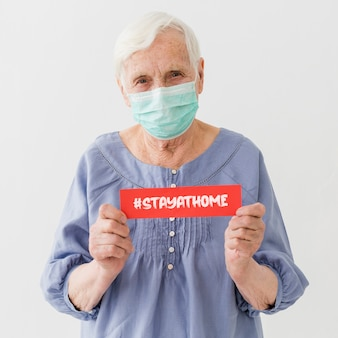 Front view of elder woman with medical mask holding message