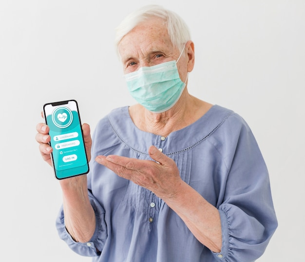 Front view of elder woman with medical mask holding smartphone