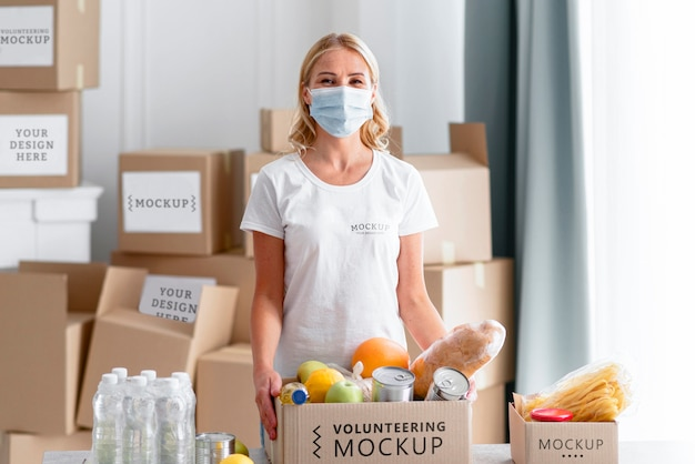 Vista frontale del volontario femminile con maschera medica che prepara donazioni di cibo