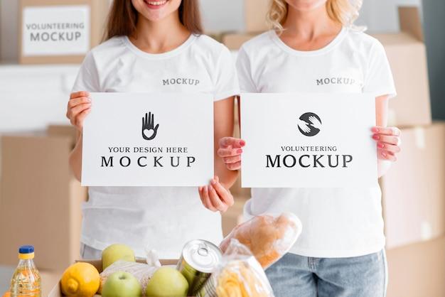 Vista frontale di volontari femminili in possesso di documenti in bianco accanto alla scatola di cibo