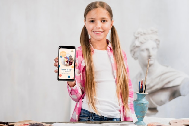 Front view of girl artist with smartphone