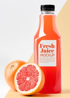 Front view glass juice bottle with grapefruit