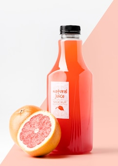 Front view glass juice bottle with grapefruits