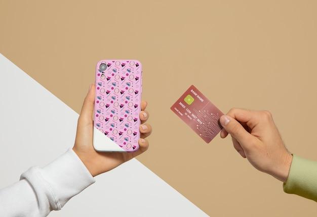 Vista frontale dello smartphone e della carta di credito tenuti in mano